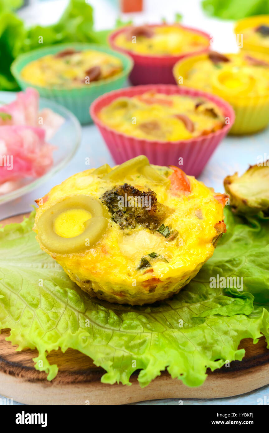 Omelette with colored pasta, mushrooms, vegetables and herbs, cooked in the form of mafins.  Breakfast. - Stock Image