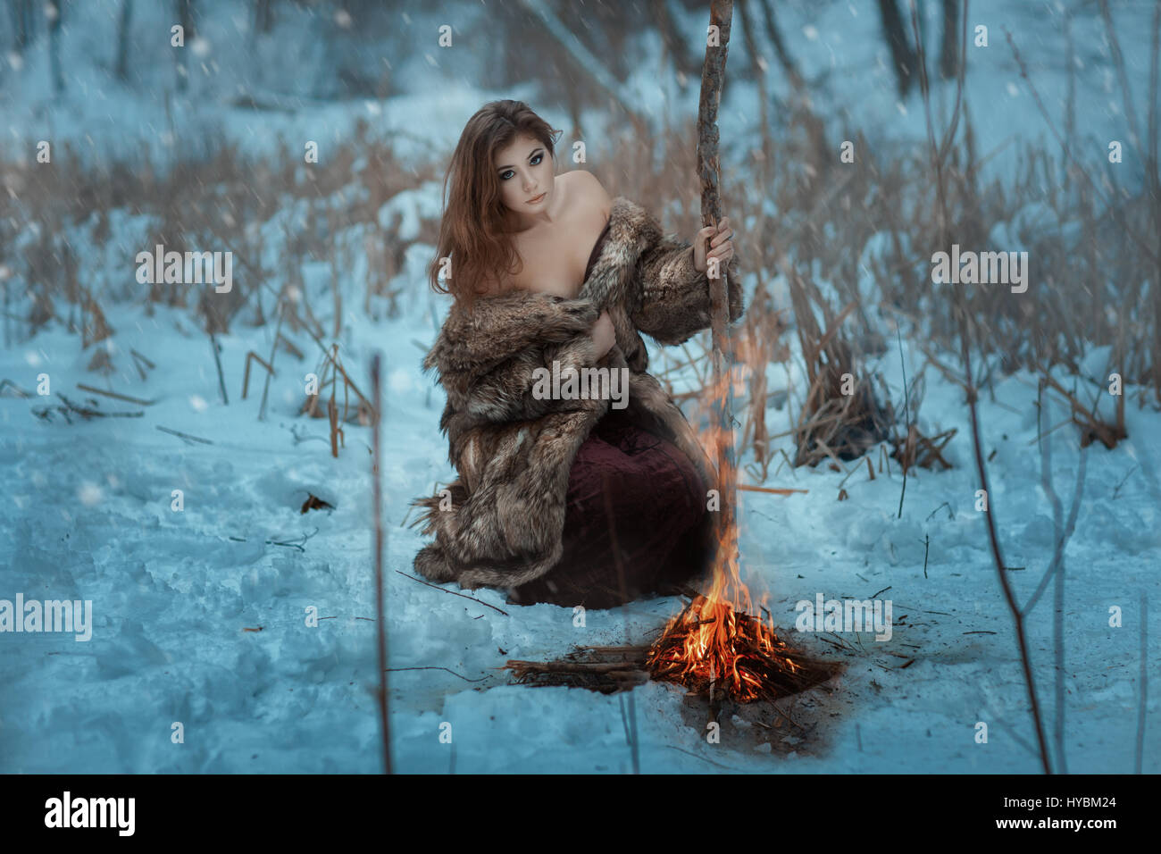 Girl shaman is heated by the fire in winter in the forest. Blizzard sweeps, and it is snowing. - Stock Image