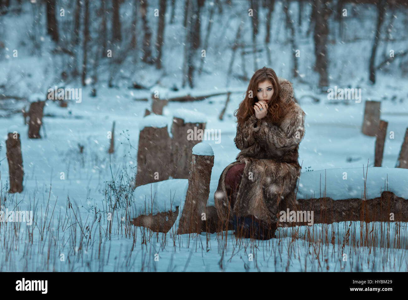 Girl is breathing on his hands warming them in winter. - Stock Image