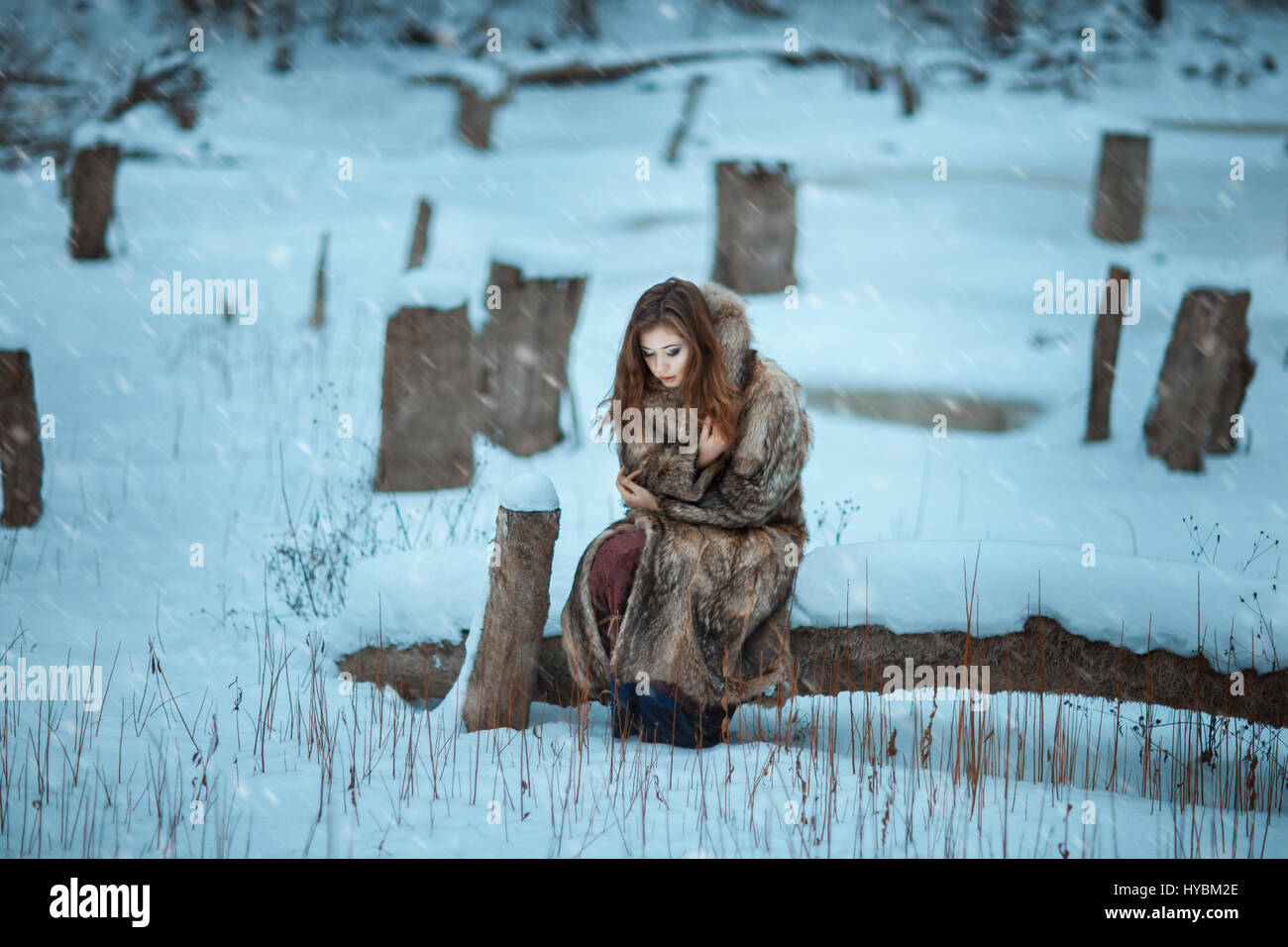 Girl froze in the winter woods. Around covered with snow and it is cold. - Stock Image