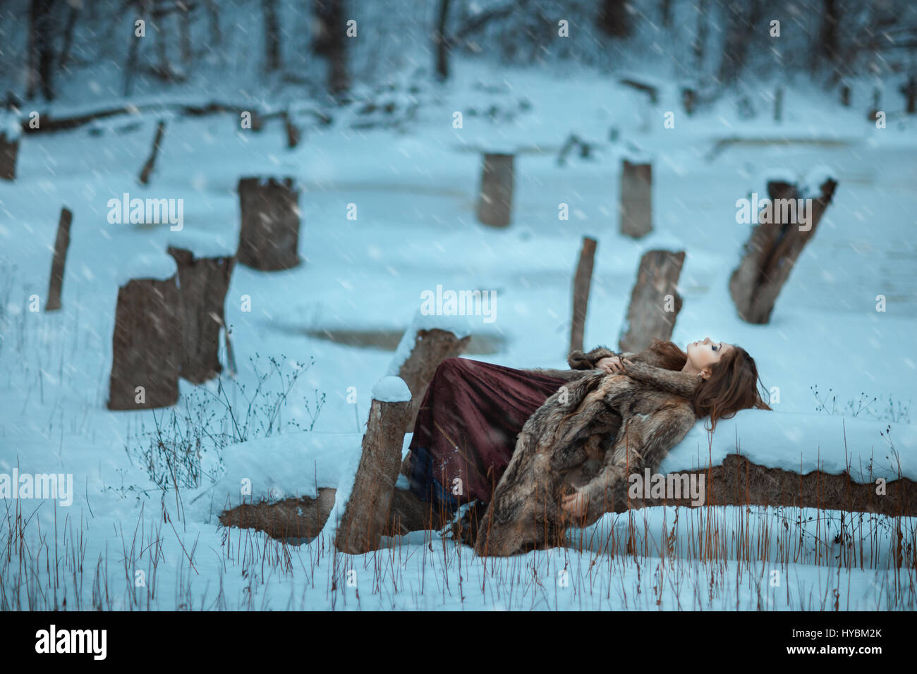 Girl lay on a tree and freeze in winter. She is alone in the woods among the drifts of snow. - Stock Image