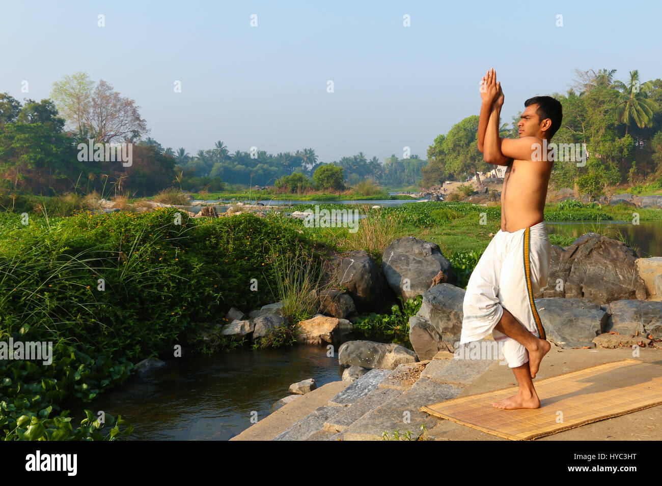 Indian man practicing yoga next to a river  in South India. - Stock Image