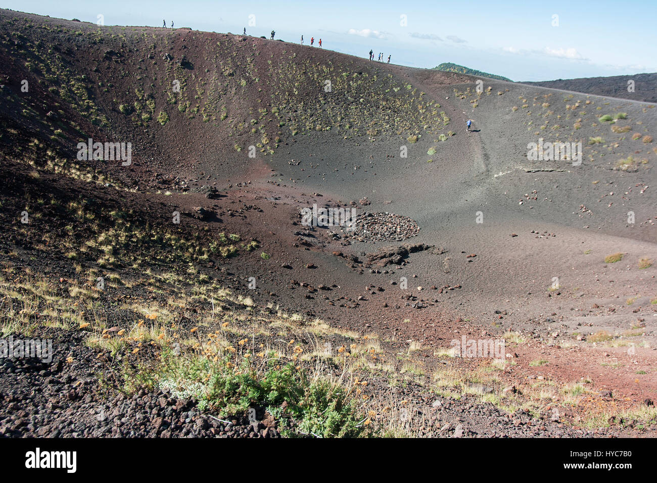A crater on Mount Etna, Sicily, with sightseers on distant rim - Stock Image