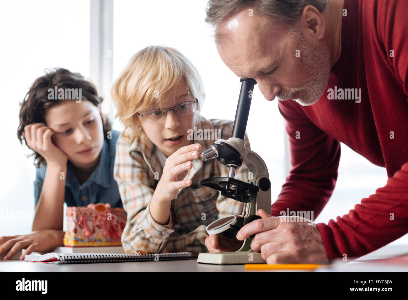 Interested awesome teacher having a look at the experiment - Stock Image