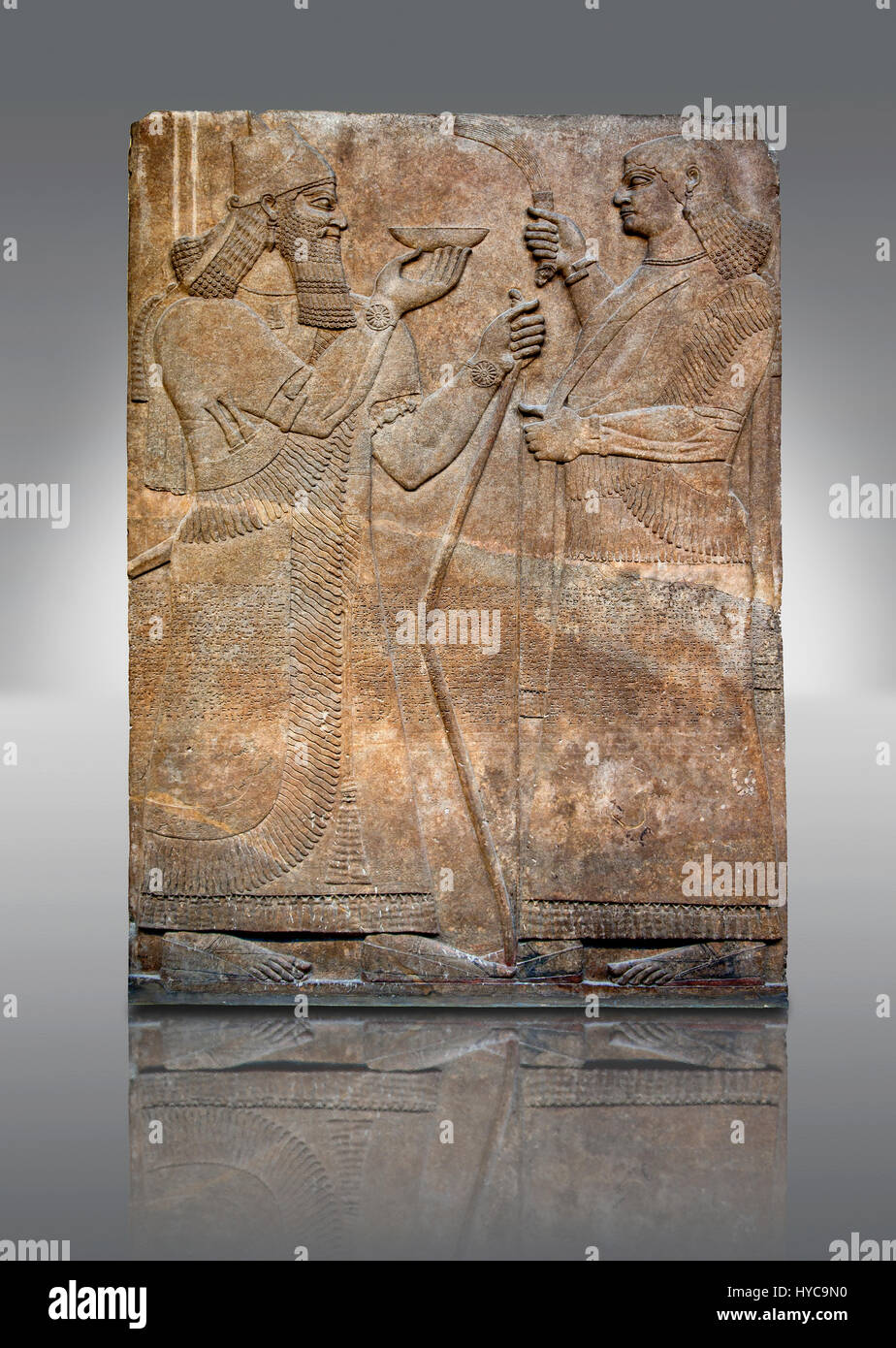 Assyrian relief sculpture panel  of King  Ashurnasirpal II demonstrating his perfect kingship by raising a ritual Stock Photo