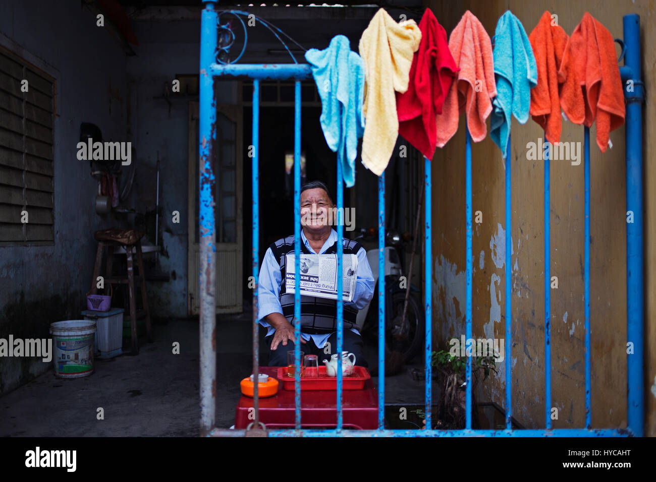 man sitting with news paper, hoian, vietnam - Stock Image