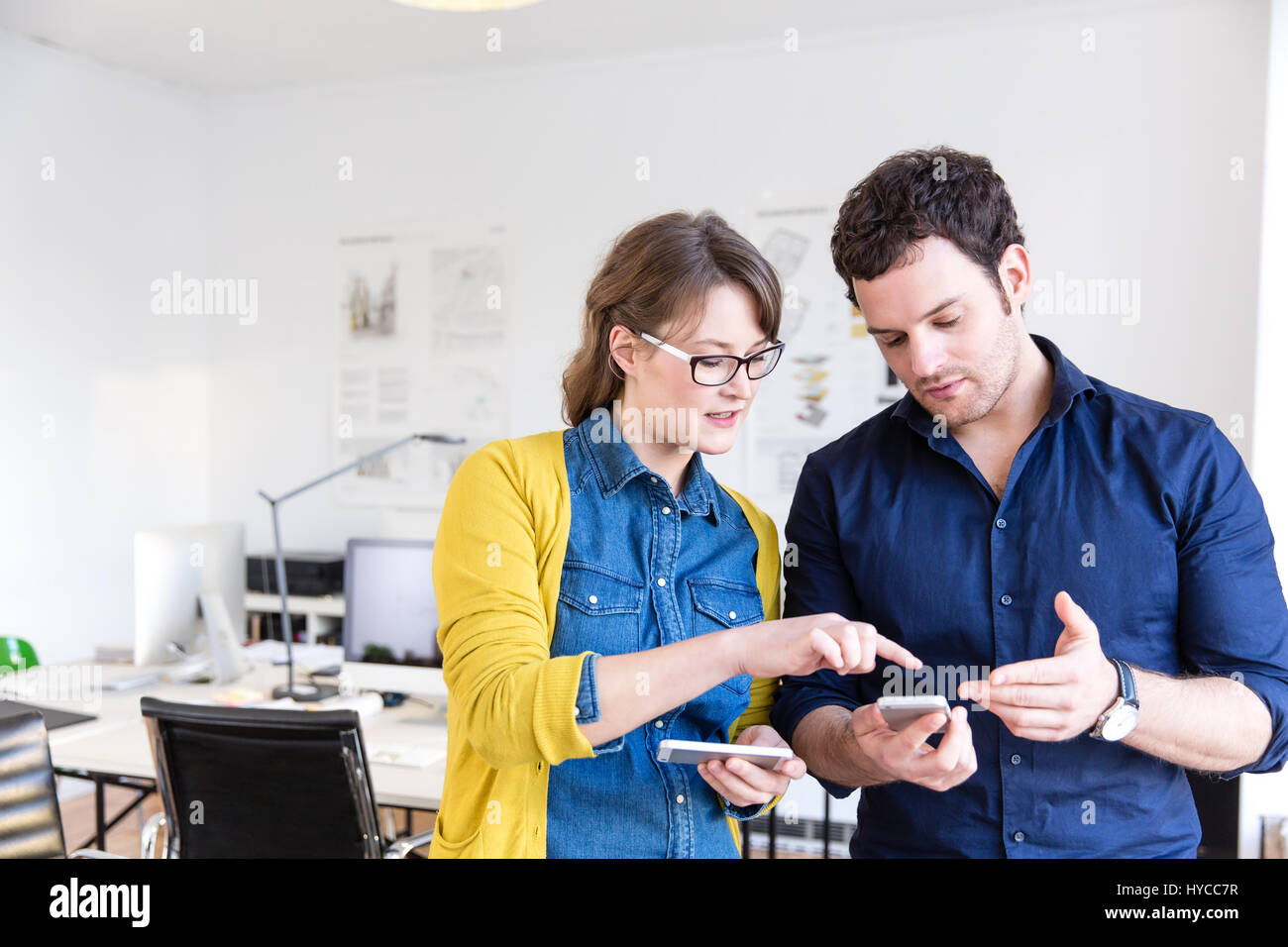 Colleagues in office looking down discussing smartphones - Stock Image