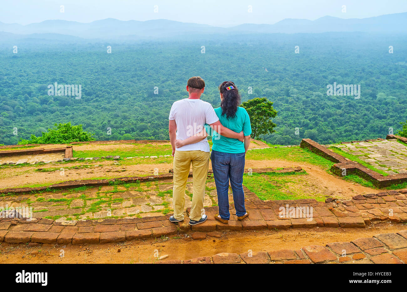 The couple enjoys the view from the top of Sigiriya Rock, hugging among the ruins of ancient upper palace, Sri Lanka. - Stock Image