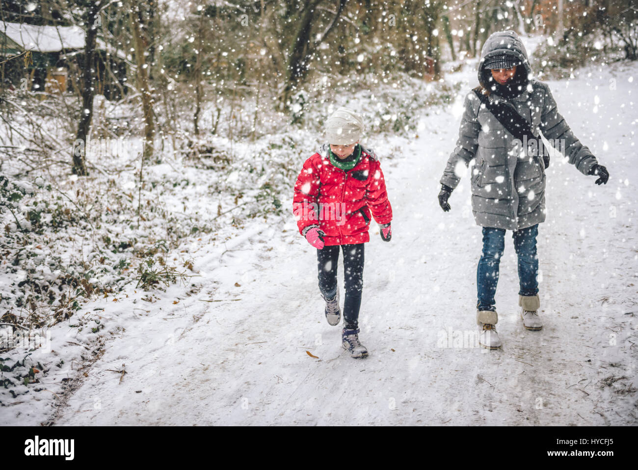 Mother with daughter hiking in white winter forest - Stock Image