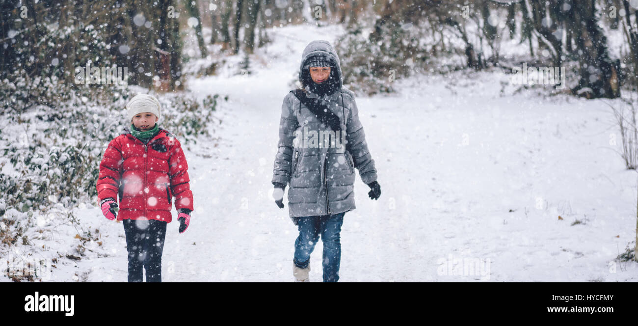 Mother with daughter hiking in white winter forest Stock Photo