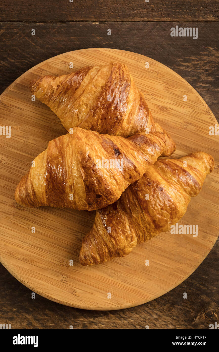 Three crunchy croissants on wooden board with copyspace - Stock Image