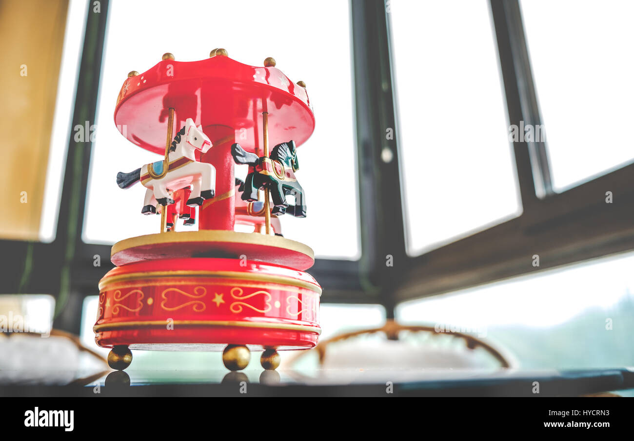 retro filtered toy music box red toned merry go round carousel horses - Stock Image