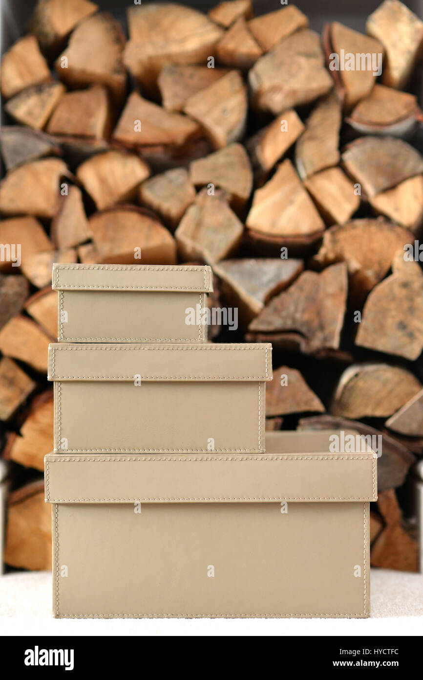 Tan leather storage boxes in front of chopped logs - Stock Image