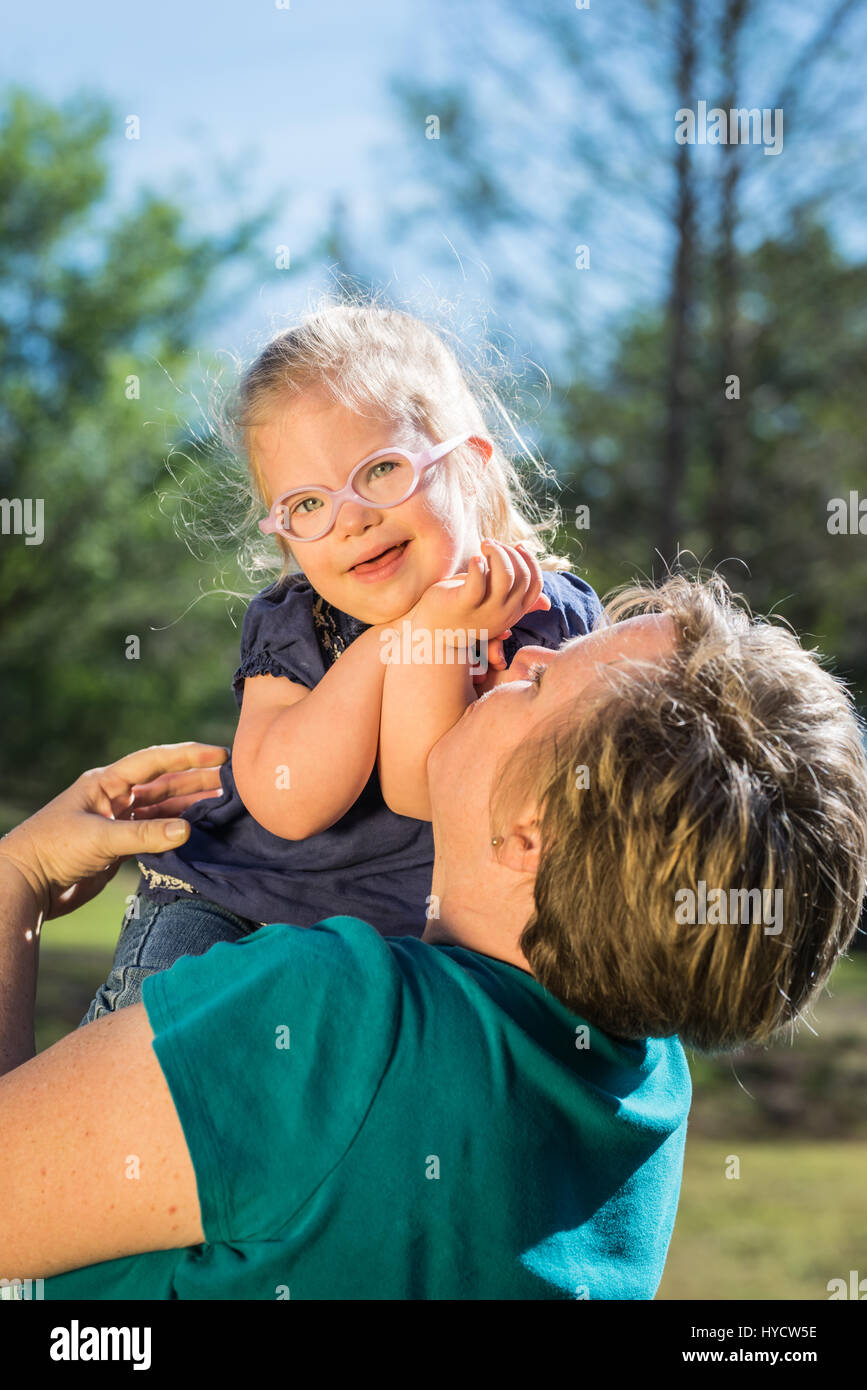 Mother holding down syndrome toddler child daughter - Stock Image