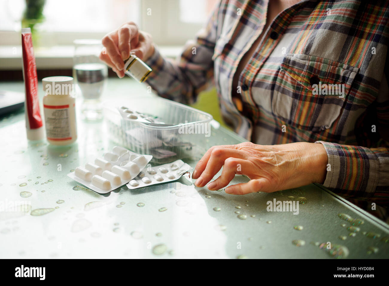 The woman having rheumatoid arthritis takes medicine. Hands are deformed. - Stock Image