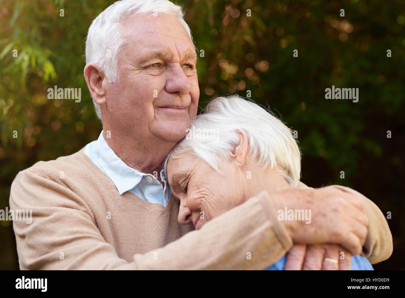 Romantic senior man warmly hugging his woman outside - Stock Image