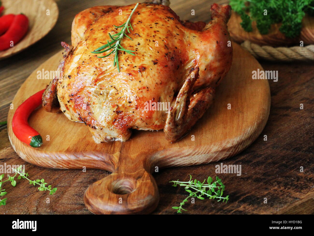 Whole roasted chicken on cutting board - Stock Image