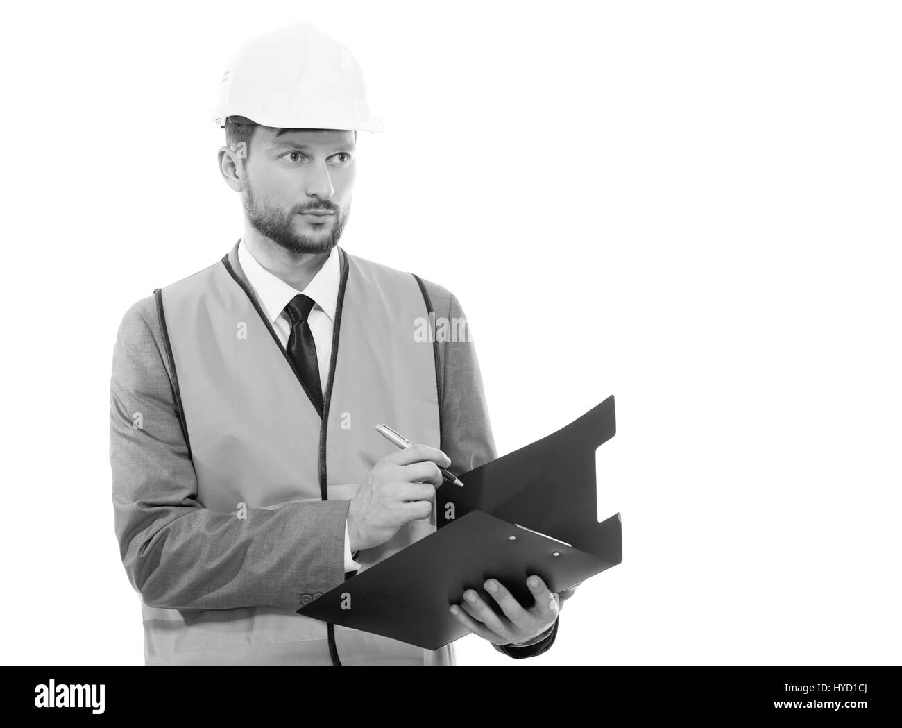 Male architect in a safety west and a hardhat writing on his cli - Stock Image