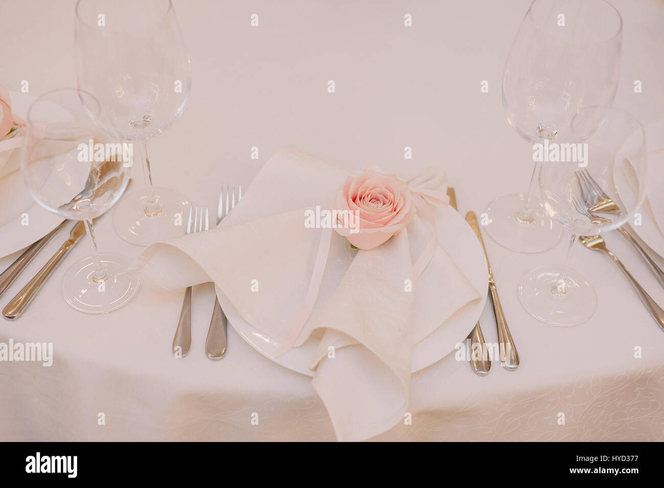 Wedding table decoration of the napkin with the light pink rose on the plate - Stock Image