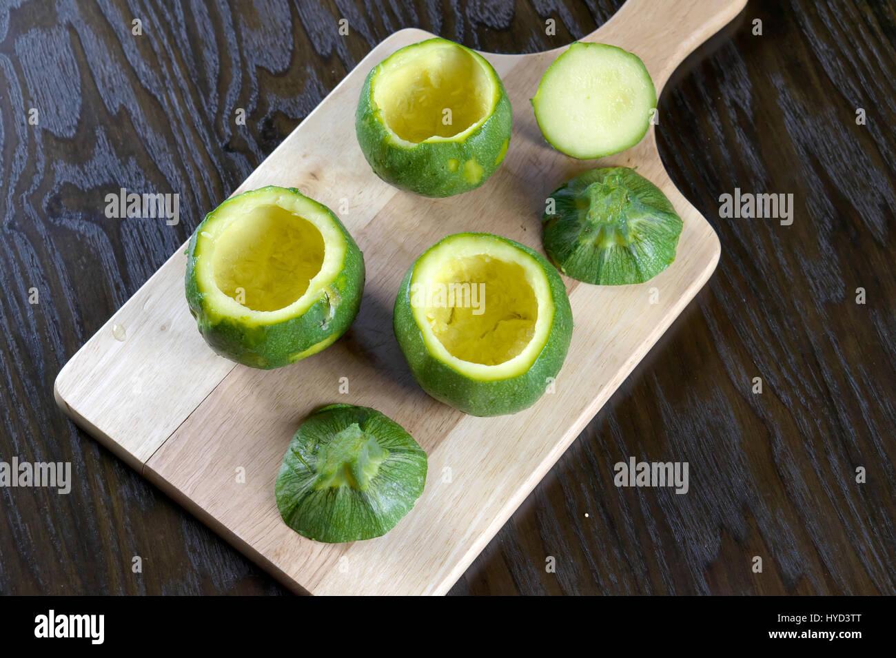 Emptied round zucchini on wooden cutting board lying on dark wooden table - Preparing stuffed zucchini recipe - Stock Photo