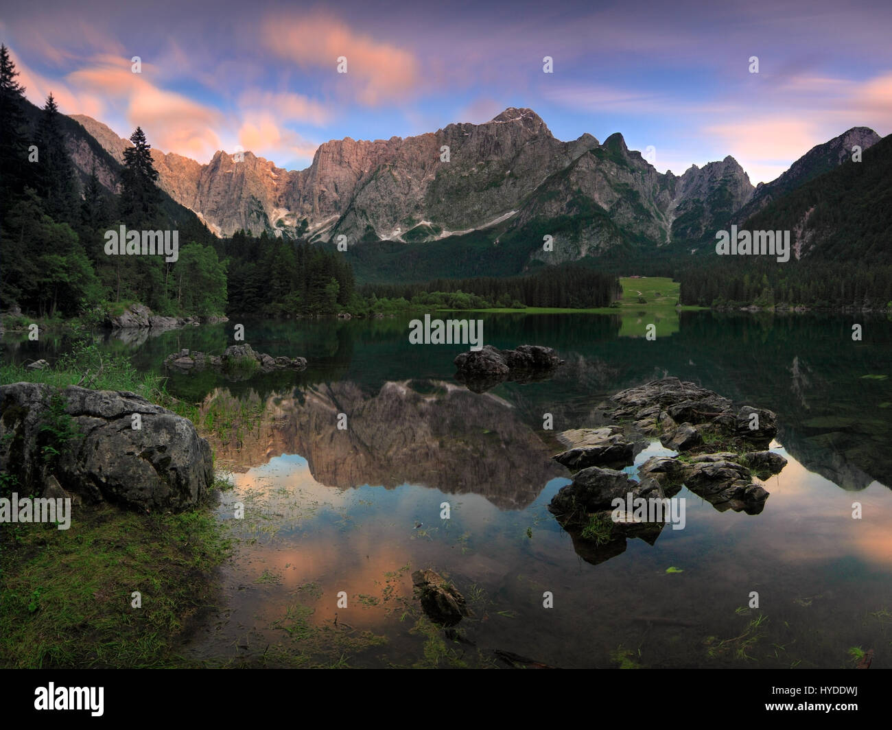 An after sunset view of the upper lake of Fusine Valromana next to Tarvisio in Friuli, Italy, with Mount Mangart - Stock Image