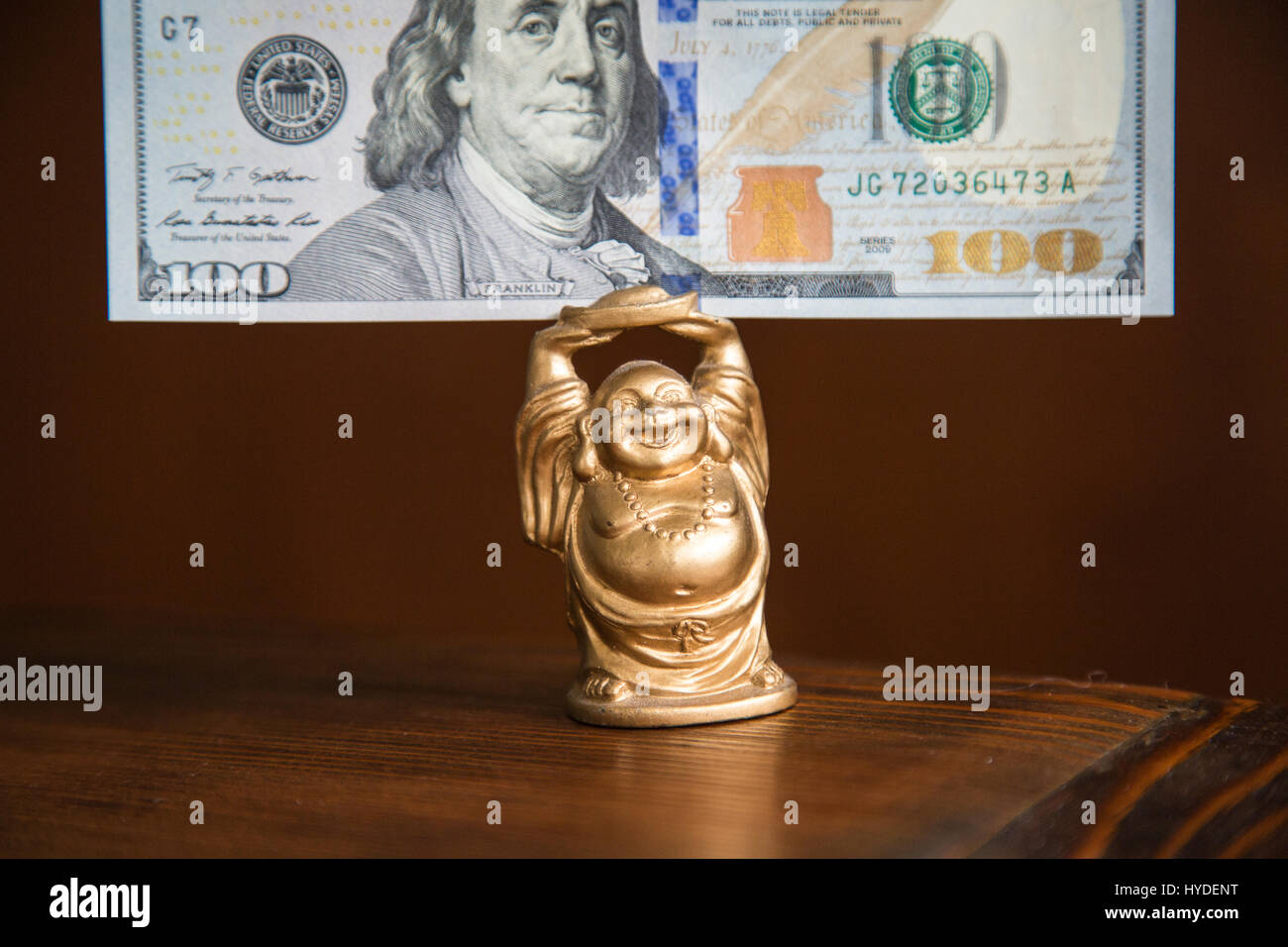 a small golden buddha figurine standing on a wooden table holds a one hundred dollar bill in United States currency - Stock Image