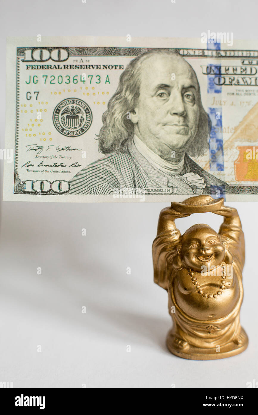 a small golden buddha figurine standing on a white back ground holds a one hundred dollar bill in United States - Stock Image