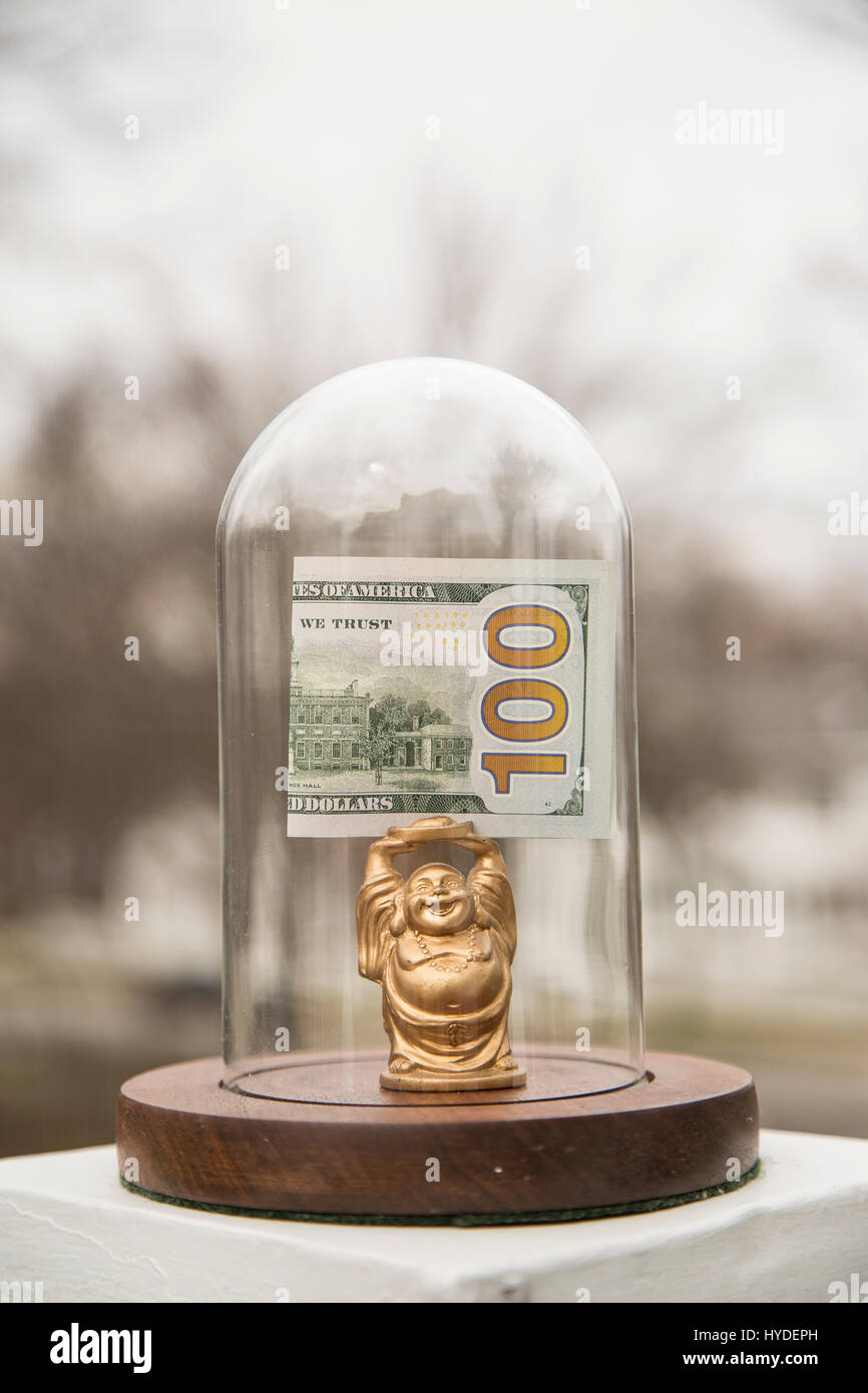 a small golden buddha figurine standing in a glass display dome holds a folded one hundred dollar bill above his - Stock Image