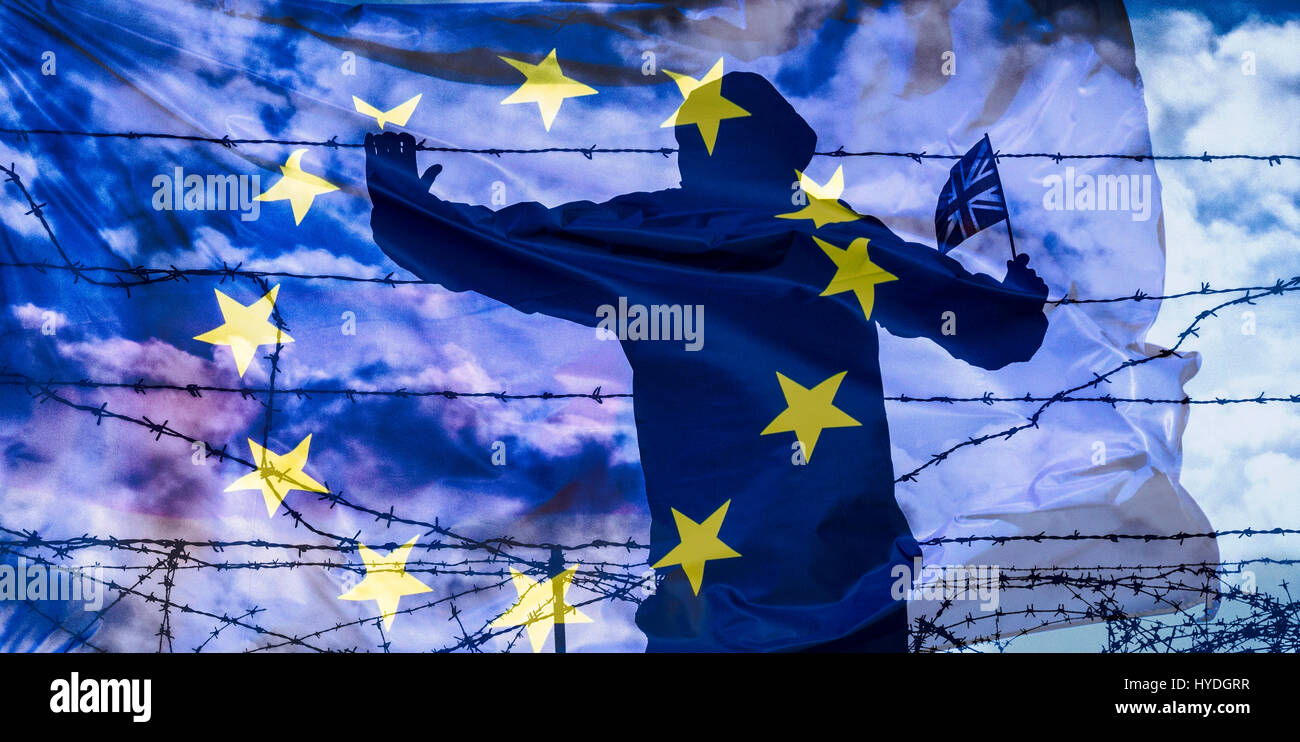 Brexit, immigration, asylum seekers... concept image. Rear view of man looking through barbed wire fence - Stock Image