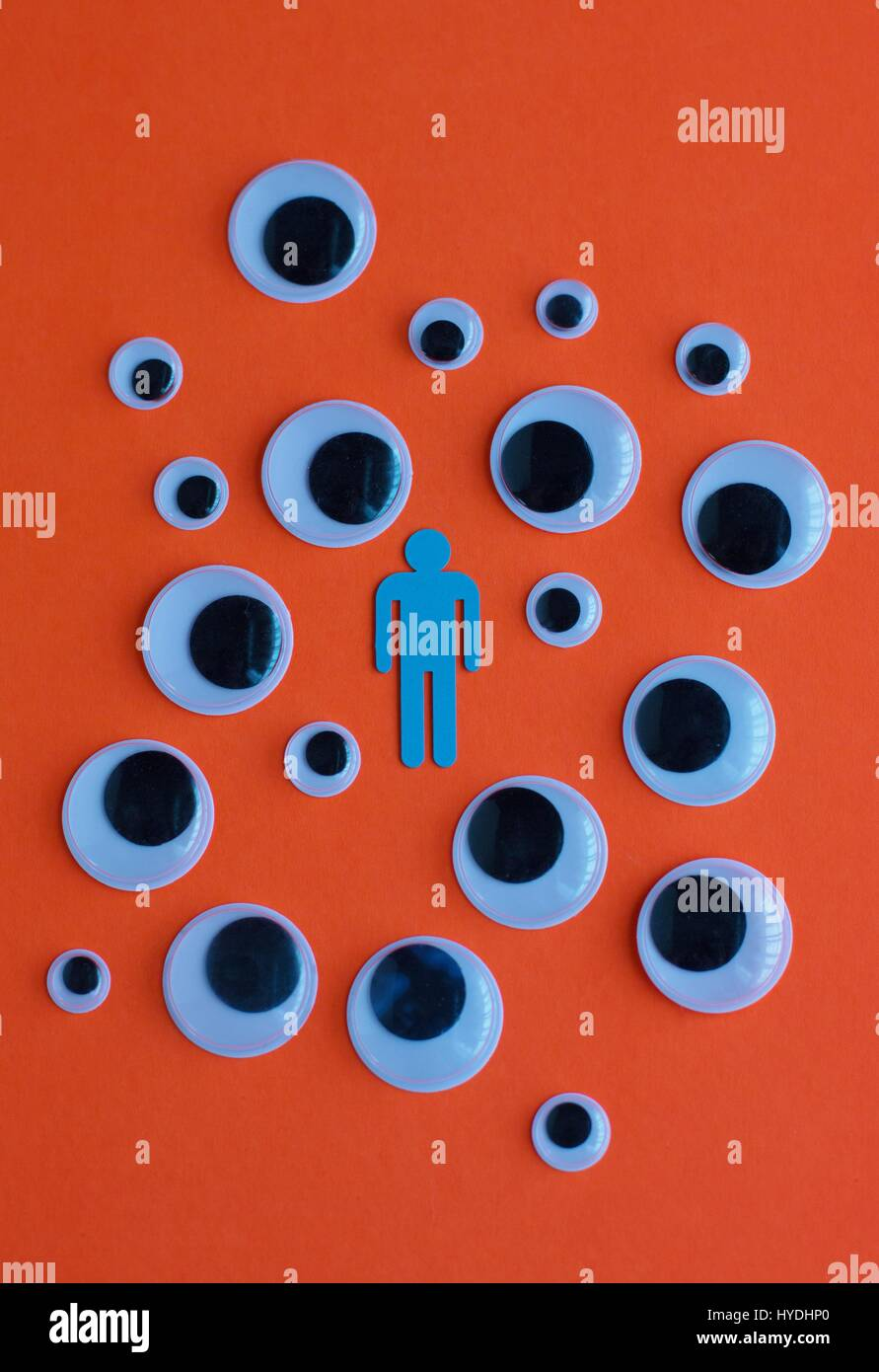 The figure of a man surrounded by eyeballs looking at him. - Stock Image