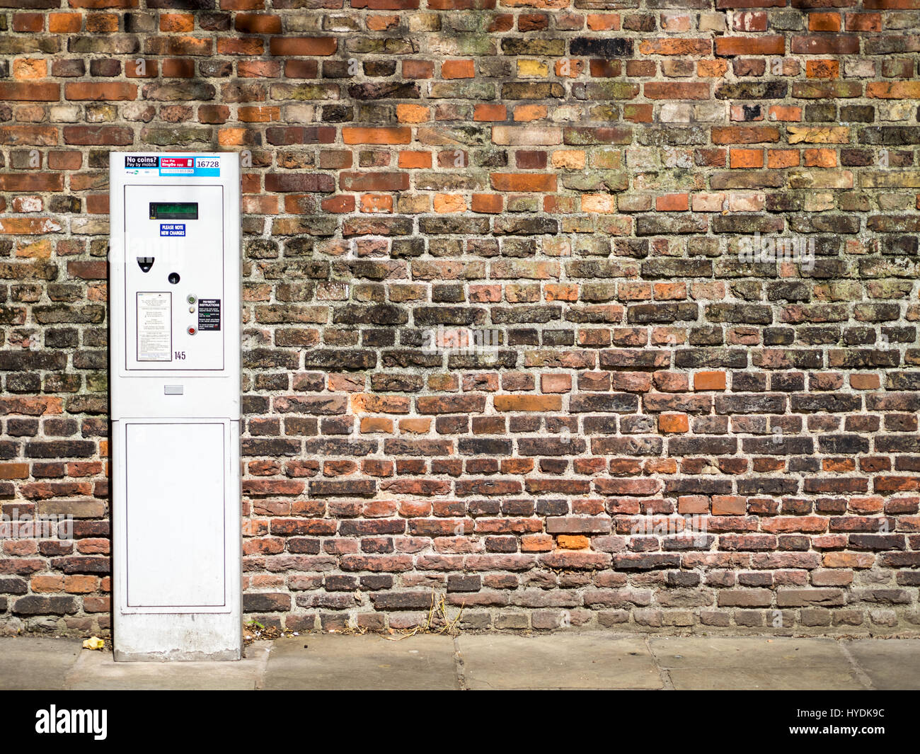 Parking Ticket machine against an old brick wall outside Jesus College, Cambridge, UK Stock Photo