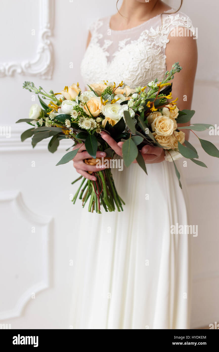 Bride holding a bouquet of flowers in a rustic style wedding stock bride holding a bouquet of flowers in a rustic style wedding bouquet bride with bouquet in the white room izmirmasajfo