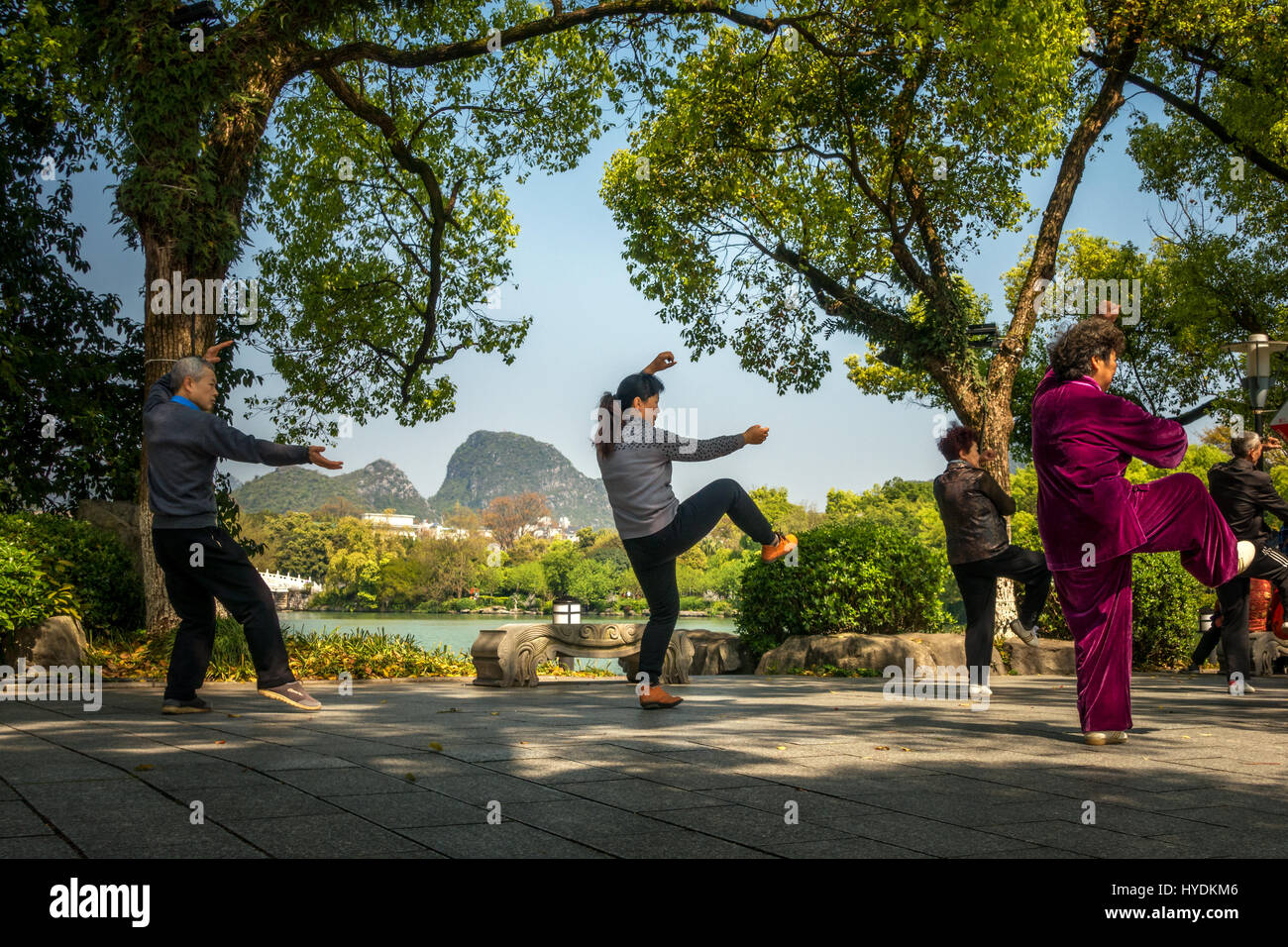 People enjoying Tai Chi exercise beside the water in Guilin, China - Stock Image