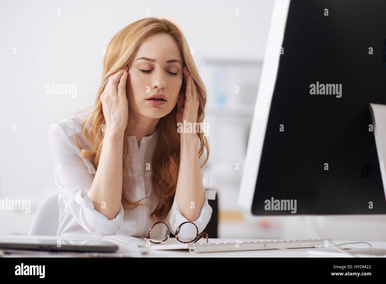 Disappointed young office manager having headache in the office - Stock Image