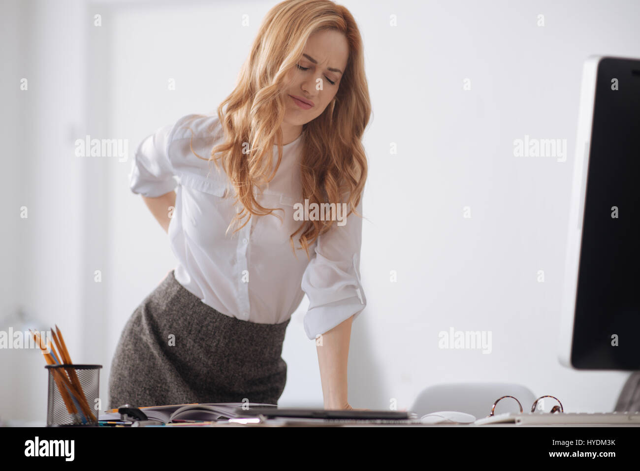 Stressed young manager touching her aching back in the office - Stock Image