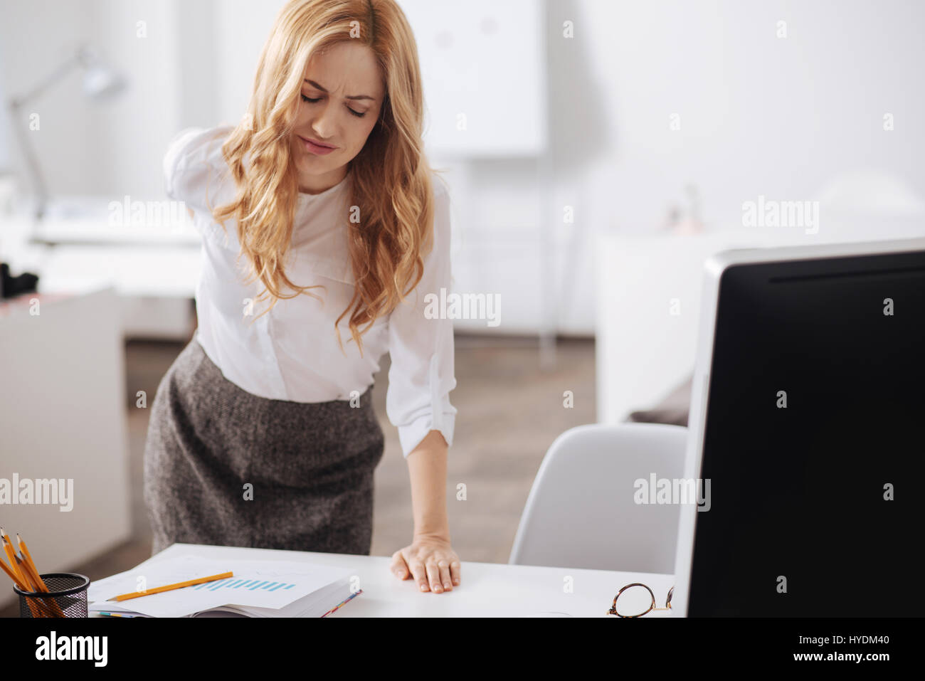 Distracted young woman feeling pain in her back in the office - Stock Image