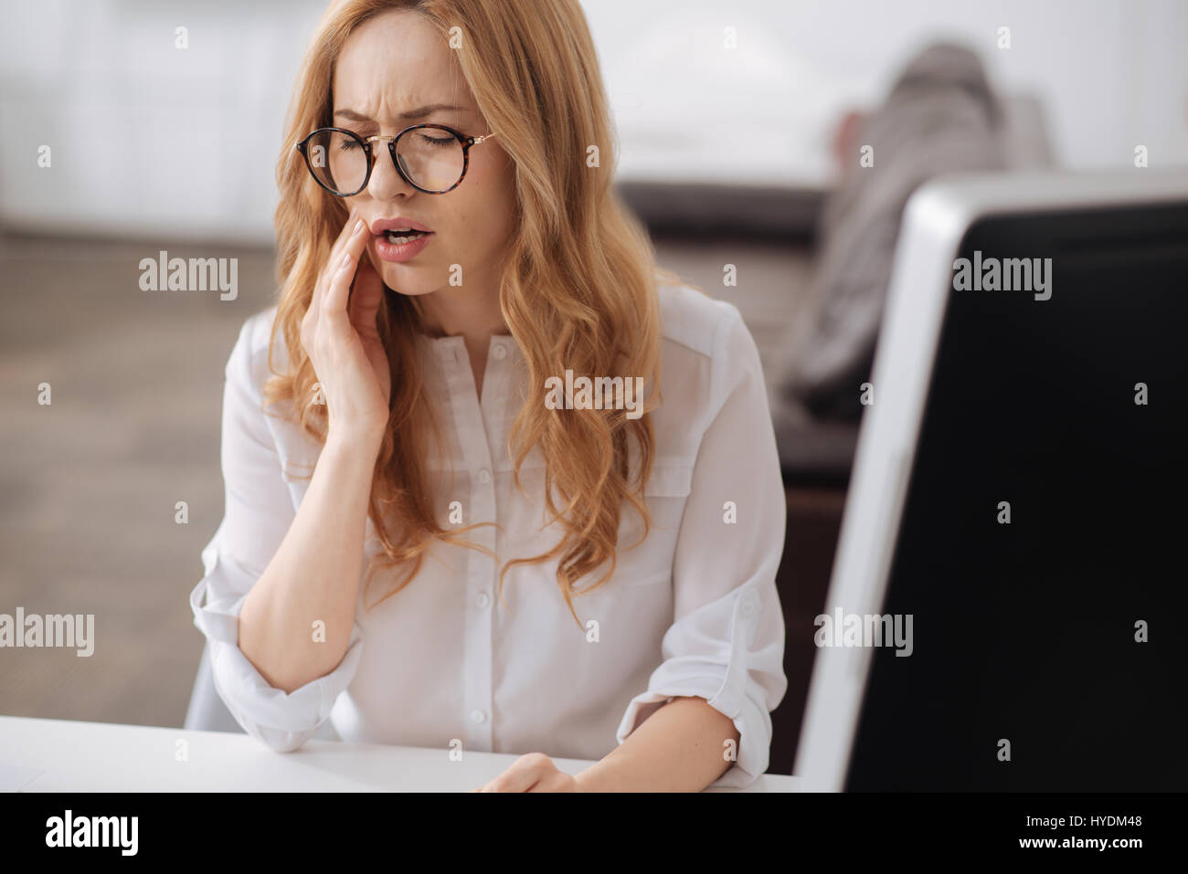 Frustrated young secretary suffering from aching teeth in the office - Stock Image