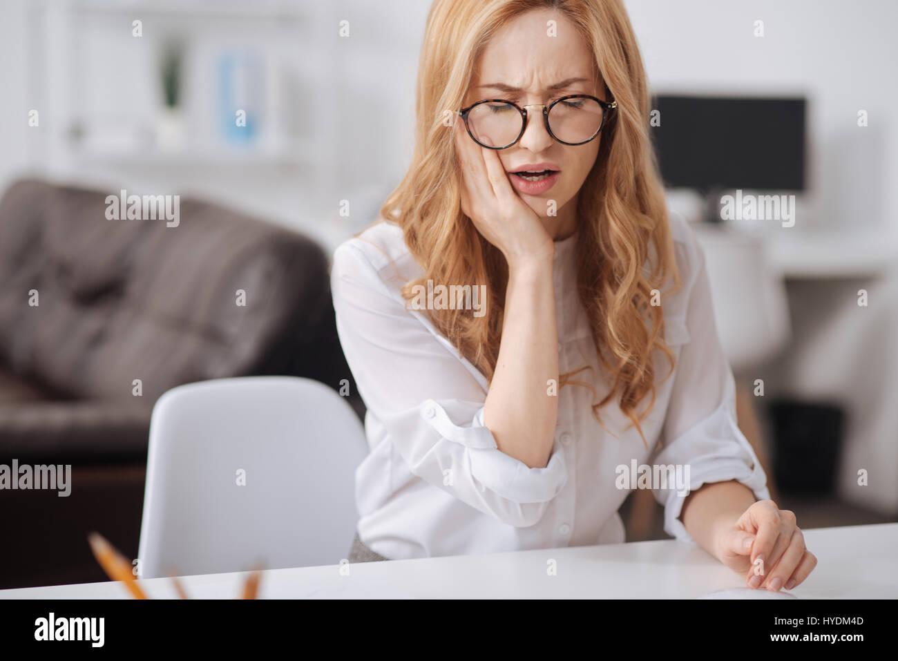 Unhappy young worker suffering from aching teeth in the office - Stock Image