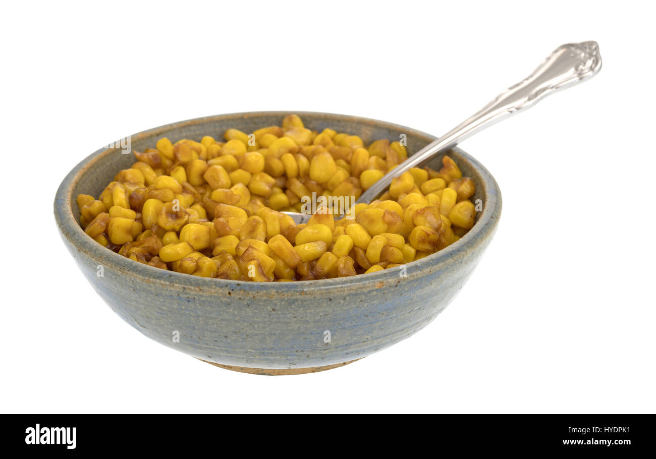 An old stoneware bowl filled with barbecue flavored cut corn and a spoon in the food isolated on a white background. - Stock Image