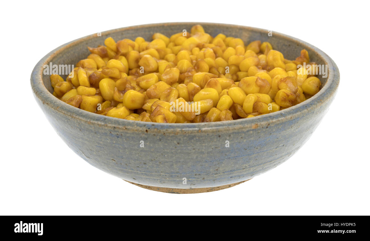 An old stoneware bowl filled with barbecue flavored cut corn isolated on a white background. - Stock Image