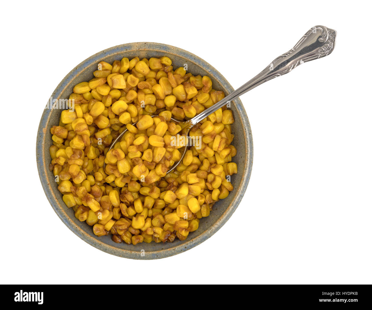 Top view of an old stoneware bowl filled with barbecue flavored cut corn and a spoon in the food isolated on a white - Stock Image