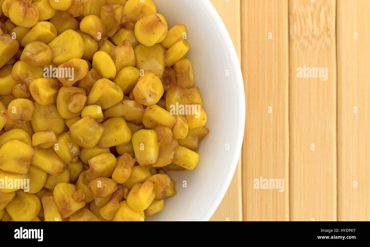 Top close view of a white bowl filled with barbecue flavored cut corn on a wood place mat. - Stock Image