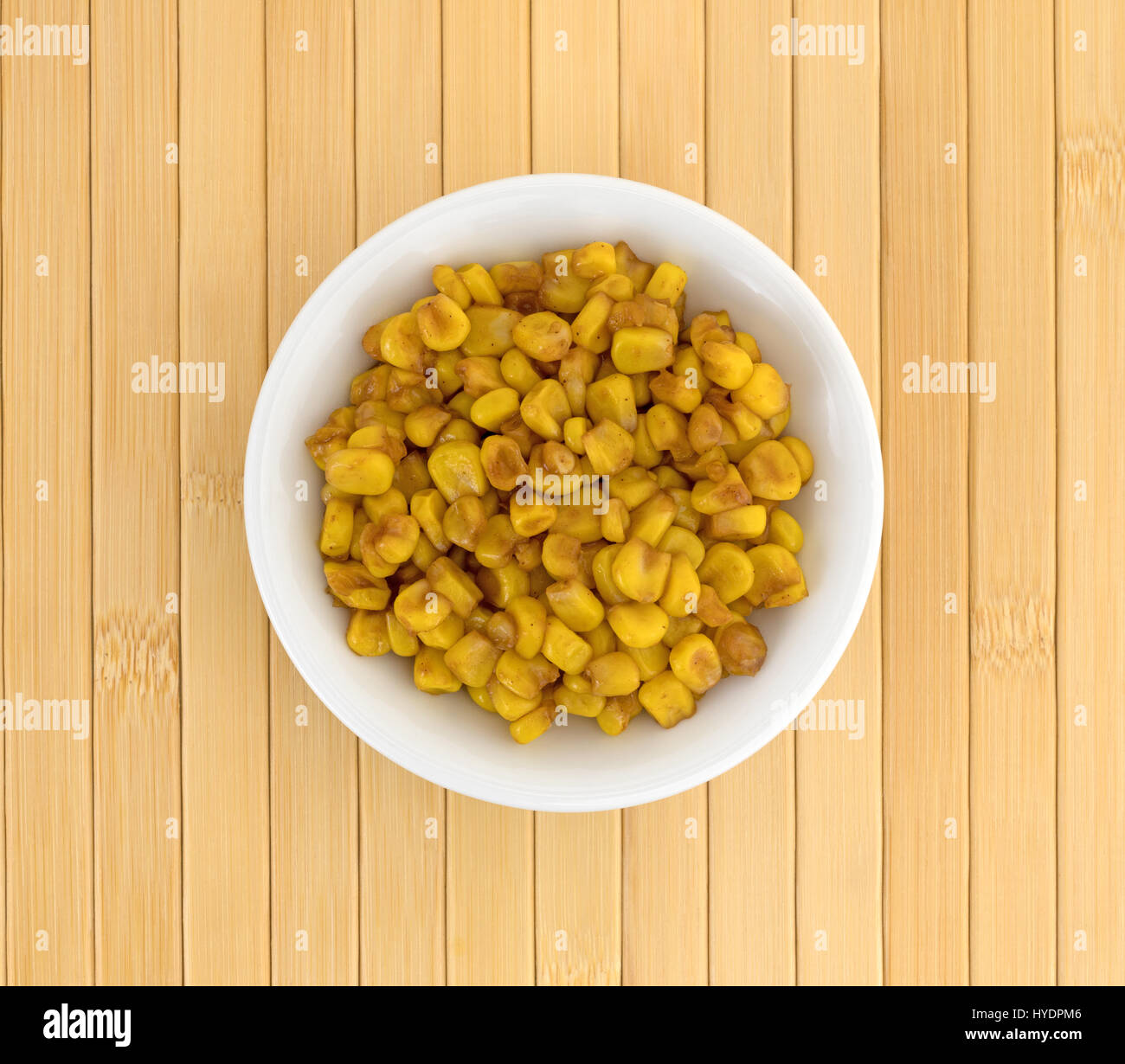 Top view of a white bowl filled with barbecue flavored cut corn on a wood place mat. - Stock Image