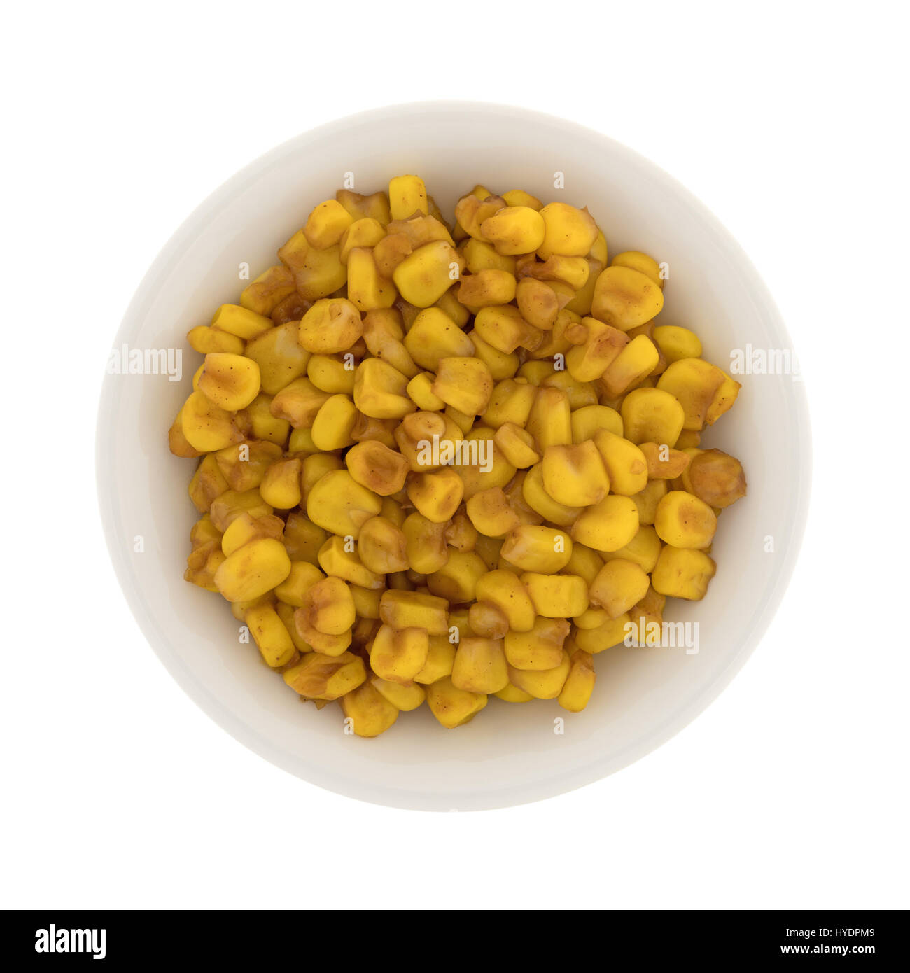Top view of an small bowl filled with barbecue flavored cut corn isolated on a white background. - Stock Image