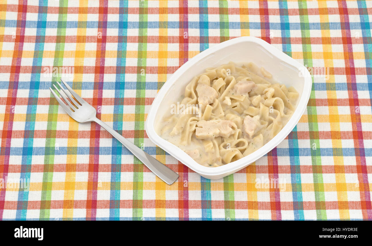 Cooked TV dinner of fettuccini with chicken and seasonings in a plastic tray plus a fork to the side atop a cloth - Stock Image