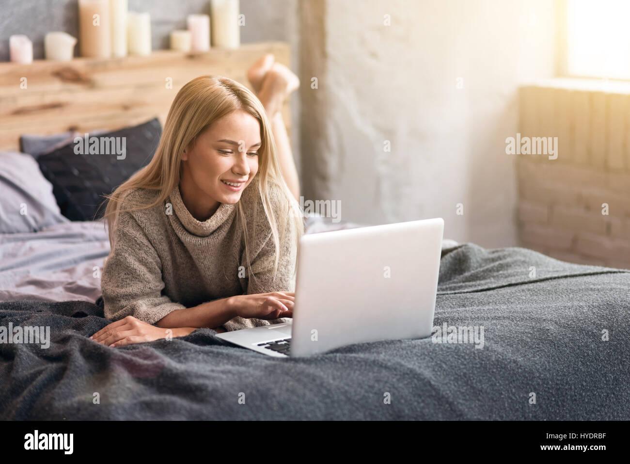 Gentle young woman enjoying freelance job at home - Stock Image