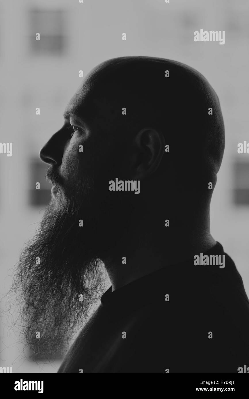 Profile portrait of man with shaved head - Stock Image