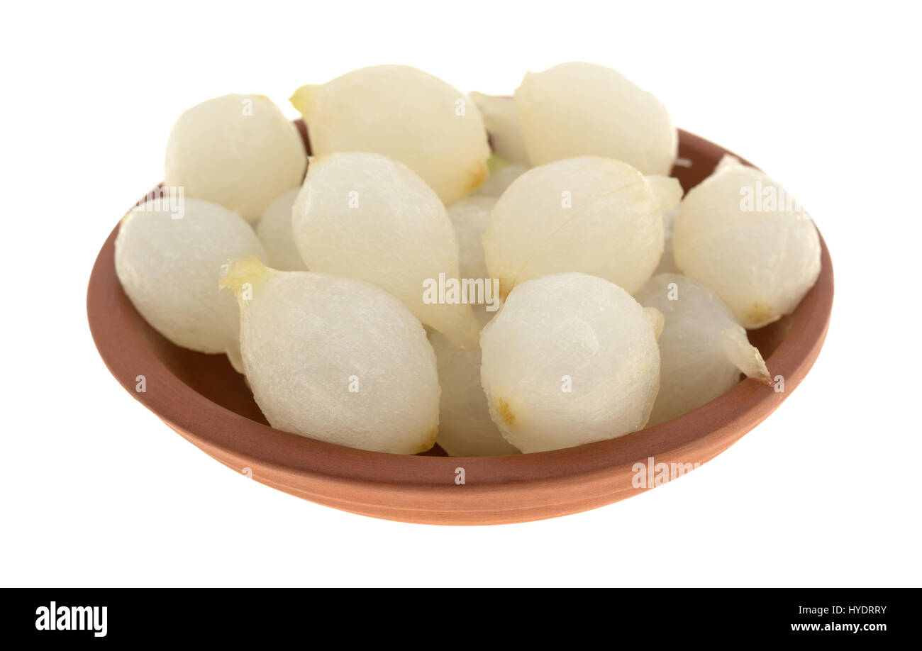A small clay bowl filled with cooked pearl onions isolated on a white background. - Stock Image