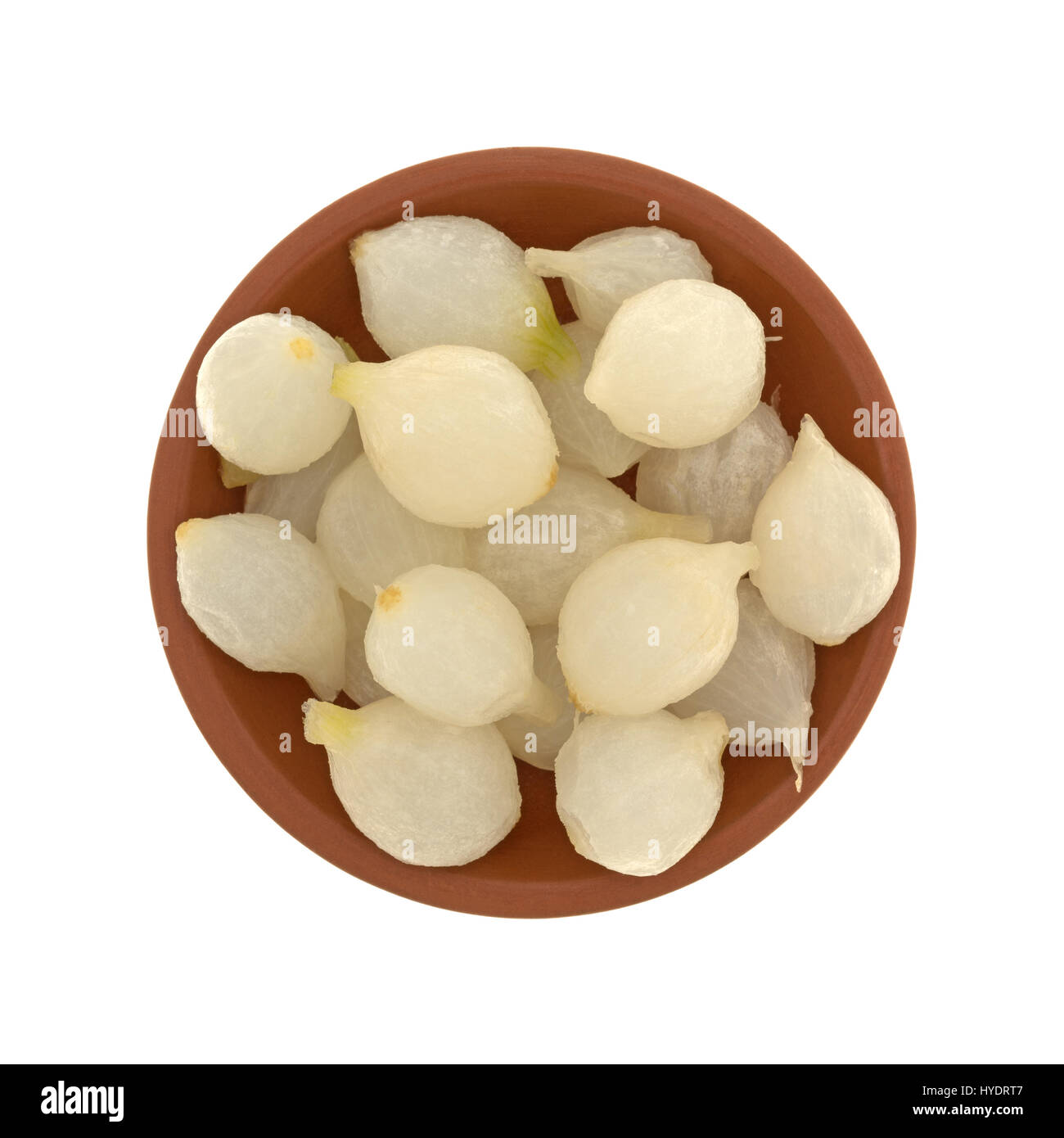 Top view of a small clay bowl filled with cooked pearl onions isolated on a white background. - Stock Image