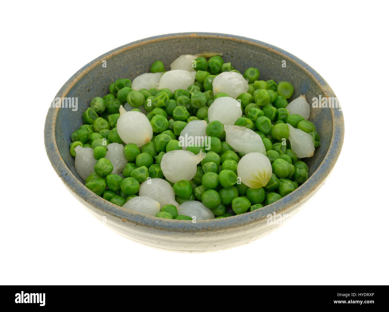 A stoneware bowl filled with cooked pearl onions and green peas isolated on a white background. - Stock Image